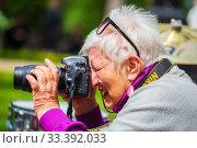 Купить «beautiful old woman photographer cheerfully takes a digital camera on a spring sunny day.», фото № 33392033, снято 18 мая 2019 г. (c) Акиньшин Владимир / Фотобанк Лори
