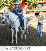 Купить «Man in helmet riding by horse at ranch, trainer talking to female», фото № 33396813, снято 4 июля 2018 г. (c) Яков Филимонов / Фотобанк Лори