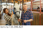 Купить «Portrait of couple cleaning horse while standing at stabling», фото № 33396821, снято 4 июля 2018 г. (c) Яков Филимонов / Фотобанк Лори