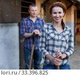 Купить «Mature positive family couple with tools standing at stabling», фото № 33396825, снято 4 июля 2018 г. (c) Яков Филимонов / Фотобанк Лори