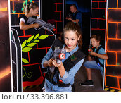 Portrait of teenager girl with laser gun having fun with her family on lasertag arena. Стоковое фото, фотограф Яков Филимонов / Фотобанк Лори