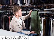 Купить «Cheerful man choosing new trousers», фото № 33397001, снято 4 апреля 2020 г. (c) Яков Филимонов / Фотобанк Лори