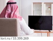Купить «Arab man watching tv at home», фото № 33399269, снято 12 марта 2018 г. (c) Elnur / Фотобанк Лори