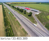 Купить «Freeway road with traffic lay-by to petrol station, wide and straight highway in plain terrain, view from above. Трасса М-4 Дон», фото № 33403389, снято 30 июля 2018 г. (c) Кекяляйнен Андрей / Фотобанк Лори