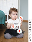 Toddler child with toy with letters, alphabet characters. Little girl sitting on floor of domestic room. Стоковое фото, фотограф Кекяляйнен Андрей / Фотобанк Лори