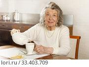 Купить «White-haired old woman pours herself a cup of tea», фото № 33403709, снято 2 февраля 2020 г. (c) Алексей Кузнецов / Фотобанк Лори