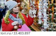 Купить «Young positive girl shopping decorations on traditional Christmas market in Spain», видеоролик № 33403897, снято 12 декабря 2018 г. (c) Яков Филимонов / Фотобанк Лори