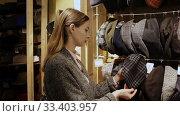 Young focused woman shopping hats in modern store. Стоковое видео, видеограф Яков Филимонов / Фотобанк Лори