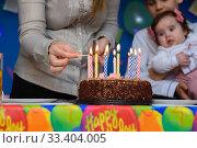 Купить «Мама зажигает свечки на торте на заднем плане дети», фото № 33404005, снято 19 марта 2020 г. (c) Иванов Алексей / Фотобанк Лори