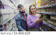 Couple choosing spanish green olives during grocery shopping at food department in supermarket. Стоковое видео, видеограф Яков Филимонов / Фотобанк Лори