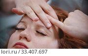 Купить «Massage - massage master massaging womans forehead with special technique using fingers», видеоролик № 33407697, снято 10 апреля 2020 г. (c) Константин Шишкин / Фотобанк Лори