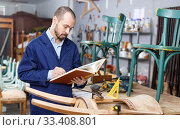 Купить «Portrait of skilled male artisan with book working at vintage furniture repair workshop», фото № 33408801, снято 19 ноября 2018 г. (c) Яков Филимонов / Фотобанк Лори