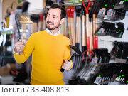 Купить «Man choosing various tools in garden equipment shop», фото № 33408813, снято 2 марта 2017 г. (c) Яков Филимонов / Фотобанк Лори