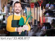 male seller showing assortment in garden equipment shop. Стоковое фото, фотограф Яков Филимонов / Фотобанк Лори