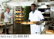 African-american baker spreads freshly baked bread on a pallet. Стоковое фото, фотограф Яков Филимонов / Фотобанк Лори