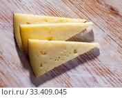Купить «Slice of semi-hard cheese on a wooden table», фото № 33409045, снято 1 апреля 2020 г. (c) Яков Филимонов / Фотобанк Лори