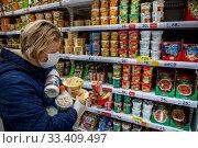 Женщина в медицинской маске делает покупки в продовольственном магазине торговой сети АШАН в торговом центре МЕГА в Химках во время коронавируса COVID-19, Россия. Редакционное фото, фотограф Николай Винокуров / Фотобанк Лори
