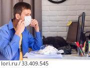 Купить «Мужчина надевает защитную медицинскую маску, работая дома за компьютером», фото № 33409545, снято 22 марта 2020 г. (c) Иванов Алексей / Фотобанк Лори