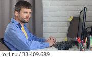 Купить «Парень отвлекся от работы за компьютером и посмотрел в окно», видеоролик № 33409689, снято 22 марта 2020 г. (c) Иванов Алексей / Фотобанк Лори