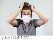 Купить «Мужчина в медицинской повязке в панике рвет на себе волосы», фото № 33411177, снято 23 марта 2020 г. (c) Кекяляйнен Андрей / Фотобанк Лори