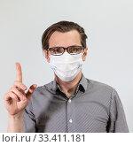 Купить «Мужчина в маске призывает к спокойствию», фото № 33411181, снято 23 марта 2020 г. (c) Кекяляйнен Андрей / Фотобанк Лори