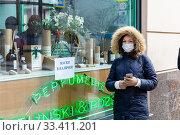 """Девушка в медицинской маске около витрины аптеки с объявлением """"Маски в наличии"""" Редакционное фото, фотограф Светлана Голинкевич / Фотобанк Лори"""