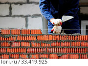 Купить «Professional construction worker laying bricks and building house on industrial site», фото № 33419925, снято 11 июля 2020 г. (c) easy Fotostock / Фотобанк Лори
