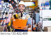 Купить «Happy male builder holding basket with tools satisfied», фото № 33422409, снято 13 сентября 2017 г. (c) Яков Филимонов / Фотобанк Лори