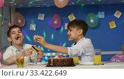 Два перепачканных мальчика смешно кушают торт за праздничным столом. Стоковое видео, видеограф Иванов Алексей / Фотобанк Лори