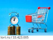 Часы стоят на стопке монет, на заднем плане продуктовая тележка. Стоковое фото, фотограф Иванов Алексей / Фотобанк Лори