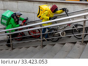 Курьеры сервисов доставки еды Delivery Club и Яндекс Еда взбираются по лестнице пешеходного перехода на Тверской улице в центре города Москвы, Россия. Редакционное фото, фотограф Николай Винокуров / Фотобанк Лори