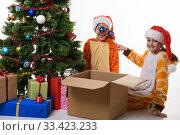Девочка повесила на шапку сестренки новогодние шарики и с улыбкой посмотрела в кадр. Стоковое фото, фотограф Иванов Алексей / Фотобанк Лори