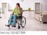 Купить «Young male invalid in wheel-chair suffering at home», фото № 33427589, снято 23 июля 2019 г. (c) Elnur / Фотобанк Лори