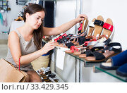 Купить «cheerful woman customer selecting shoes in footgear center», фото № 33429345, снято 26 сентября 2016 г. (c) Яков Филимонов / Фотобанк Лори