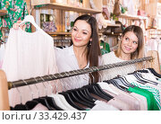 Купить «Smiling female friends choosing sweater in the modern shop», фото № 33429437, снято 15 марта 2018 г. (c) Яков Филимонов / Фотобанк Лори
