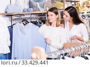 Купить «Smiling women choosing blue sweater in the modern shop», фото № 33429441, снято 15 марта 2018 г. (c) Яков Филимонов / Фотобанк Лори