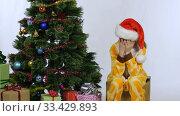 Девочка кривляется и закрыла лицо руками сидя у новогодней елки. Стоковое видео, видеограф Иванов Алексей / Фотобанк Лори