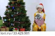 Веселая радостная девочка сидит на коробке с подарком у новогодней елки. Стоковое видео, видеограф Иванов Алексей / Фотобанк Лори
