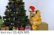 Купить «Девочка сидит на коробке возле елки после новогодних праздников и скучает», видеоролик № 33429905, снято 25 марта 2020 г. (c) Иванов Алексей / Фотобанк Лори