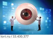 Купить «Doctor examining giant eye in medical concept», фото № 33430377, снято 9 апреля 2020 г. (c) Elnur / Фотобанк Лори