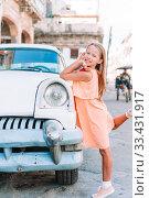 Купить «Tourist girl in popular area in Havana, Cuba. Young kid traveler smiling», фото № 33431917, снято 13 апреля 2017 г. (c) Дмитрий Травников / Фотобанк Лори