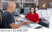Купить «Consultant helping woman choosing upholstery fabric», фото № 33438397, снято 29 октября 2018 г. (c) Яков Филимонов / Фотобанк Лори