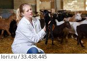 Купить «Positive farmer with goatlings on his hands», фото № 33438445, снято 15 декабря 2018 г. (c) Яков Филимонов / Фотобанк Лори