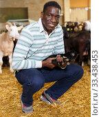 Купить «African-American man with goatlings on goat farm», фото № 33438453, снято 15 декабря 2018 г. (c) Яков Филимонов / Фотобанк Лори