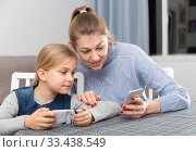 Купить «Mom and little daughter read a message on the smartphone», фото № 33438549, снято 22 января 2019 г. (c) Яков Филимонов / Фотобанк Лори