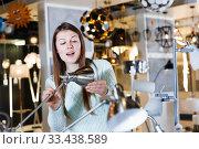 Купить «Female touching desk lamp in furniture showroom», фото № 33438589, снято 29 января 2018 г. (c) Яков Филимонов / Фотобанк Лори