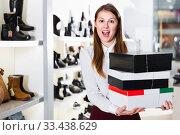 Купить «Portrait of young woman which is showing purchases in shoes store.», фото № 33438629, снято 13 декабря 2017 г. (c) Яков Филимонов / Фотобанк Лори