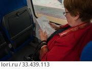 Пассажирка в вагоне поезда рассматривает схему Московского метрополитена (2016 год). Редакционное фото, фотограф Сайганов Александр / Фотобанк Лори