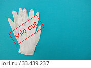Medical surgical gloves on a blue background and a sign showing SOLD OUT in red text. Coronavirus panic, purchase shortage of medical gloves, problems with stocks of medical equipment. Стоковое фото, фотограф Tetiana Chugunova / Фотобанк Лори