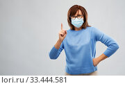 senior woman in medical mask pointing finger up. Стоковое фото, фотограф Syda Productions / Фотобанк Лори